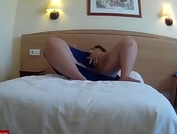 On the bed of a hotel room. RAF128